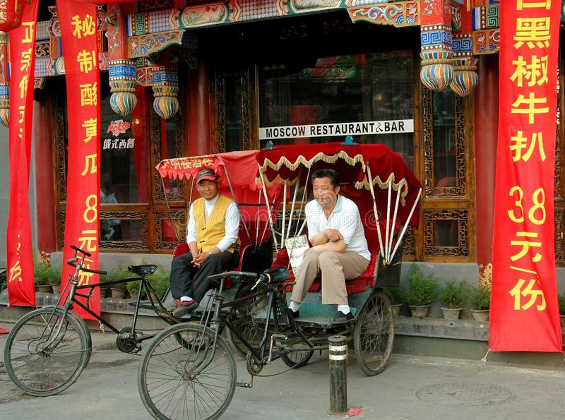 Beijing, China: Pedicab Drivers in Hutong. Two pedicab drivers waiting for a fare in front of the Moscow Restaurant & Bar in the famous Shi Sa Hai Hutong in the stock image