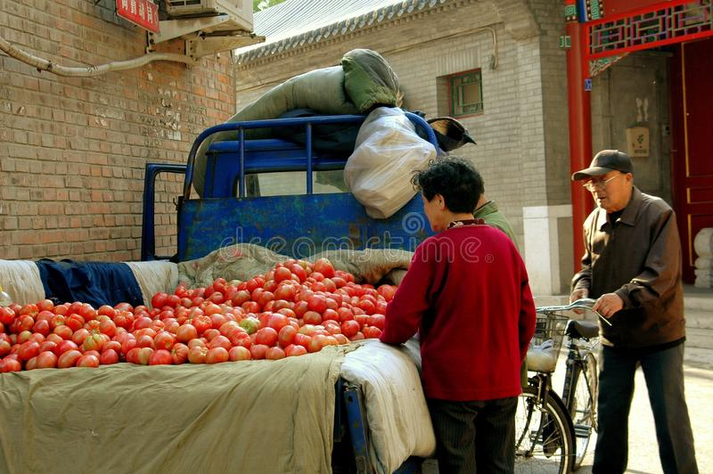 Beijing, China: People Buying Tomatoes. Husband and wife stop to buy tomatoes being sold from the back of a farm truck in the Shi Sa Hai Hutong in Beijing, China stock images