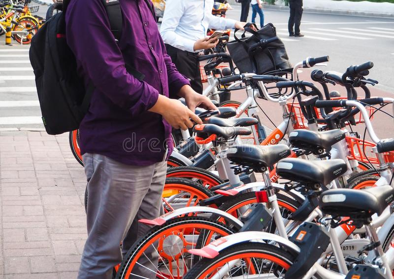 Young men using smartphones to unlock a bike stock photo