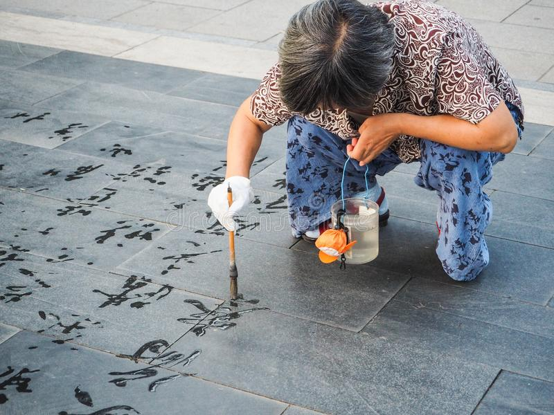 Older woman practicing water calligraphy royalty free stock images