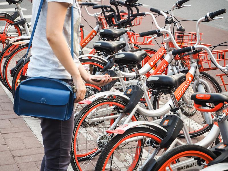 Young woman making use of the Mobike bicycle sharing system stock photos