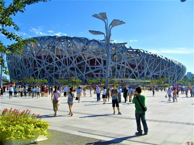 Beijing National Stadium, Bird & x27;s Nest  and tourism in China. Beijing National Stadium, Bird`s Nest and tourism in China. Sunny day, tourists, blue sky stock image