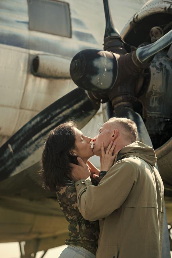 Beijo apaixonado, menino e menina dos pares Acople o beijo na frente da hélice do plano velho no dia ensolarado Pares no amor fotos de stock royalty free