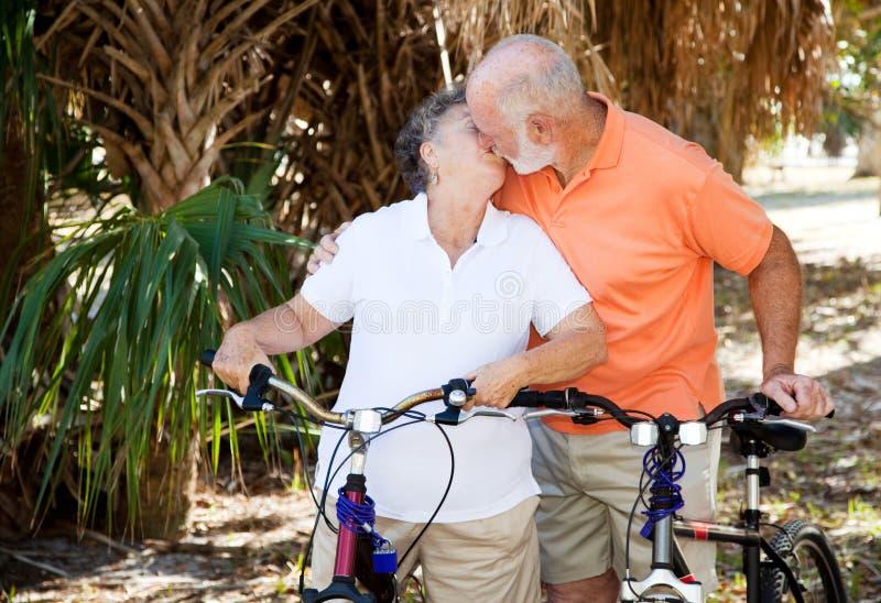 Beijo Bicycling dos séniores fotografia de stock