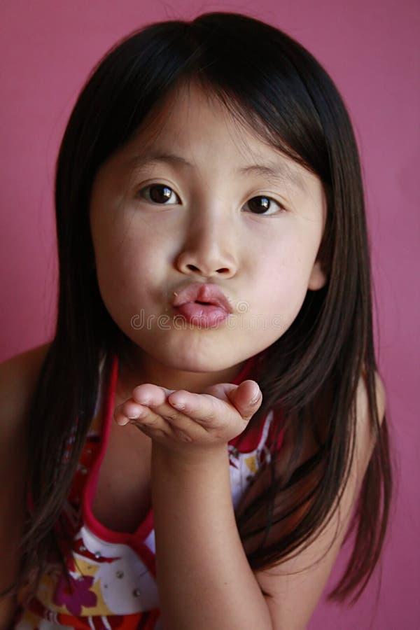Beijo de sopro da menina asiática pequena foto de stock