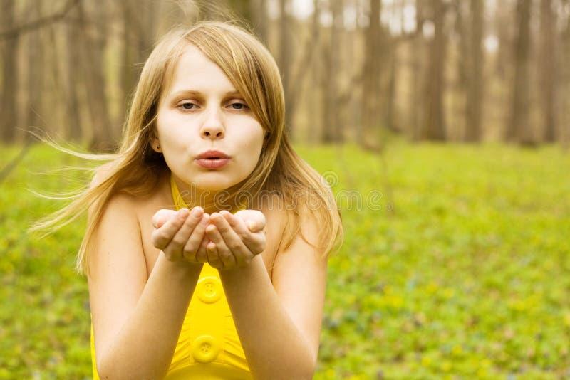 Beijo de sopro da mulher atrativa na natureza da mola imagem de stock royalty free