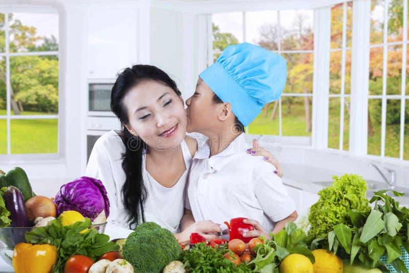 Beijo do rapaz pequeno sua mãe na cozinha fotografia de stock royalty free