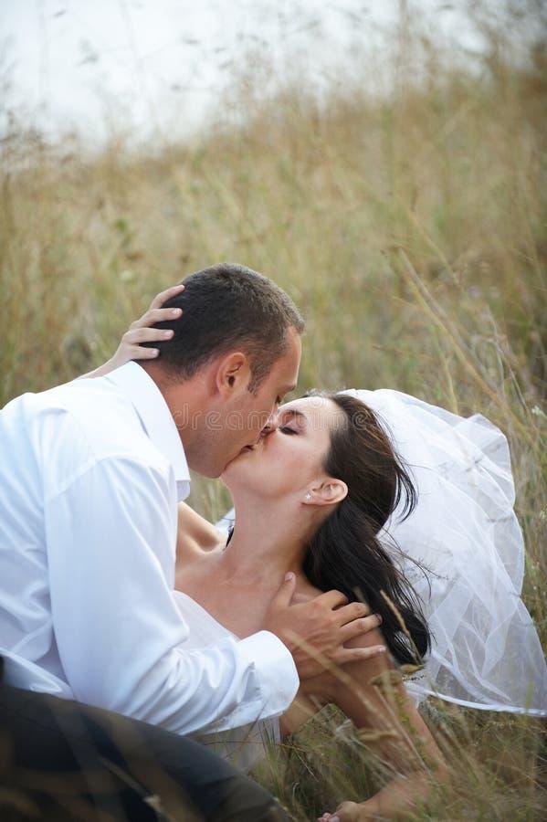 Beijo dos Newlyweds (retrato de casamento) fotografia de stock