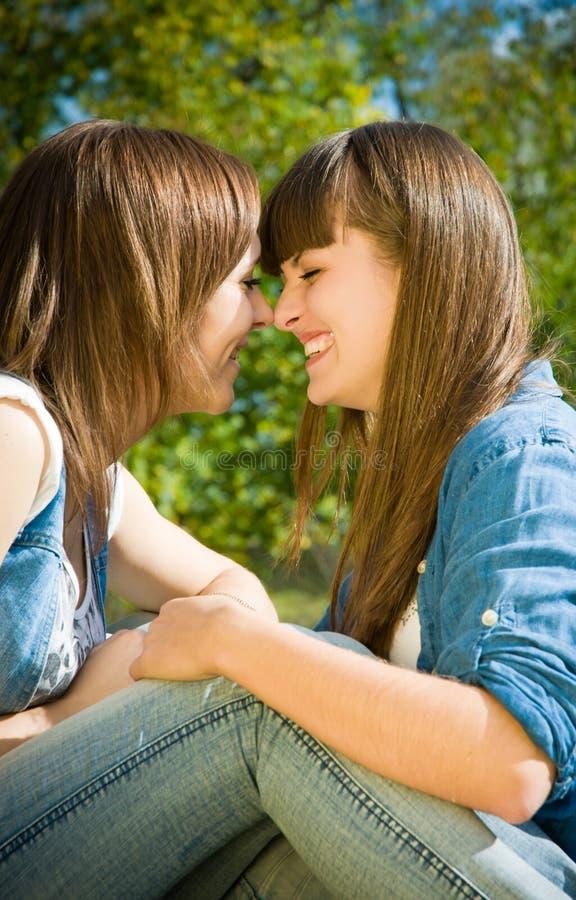 Beijo feliz de dois narizes das meninas foto de stock