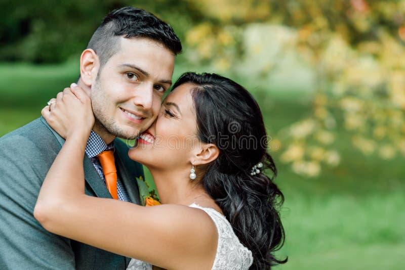 Beijo feliz dos pares do casamento foto de stock