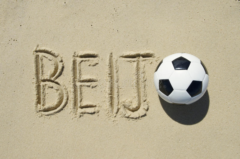 Beijo Kiss Message in Sand with Football. Football beijo (kiss in Portuguese) message with a soccer ball handwritten in sand stock image