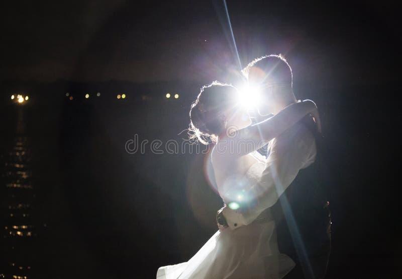 Beijo retroiluminado dos pares do casamento da noite fotografia de stock royalty free
