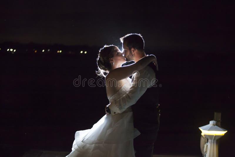 Beijo retroiluminado dos pares do casamento da noite fotos de stock