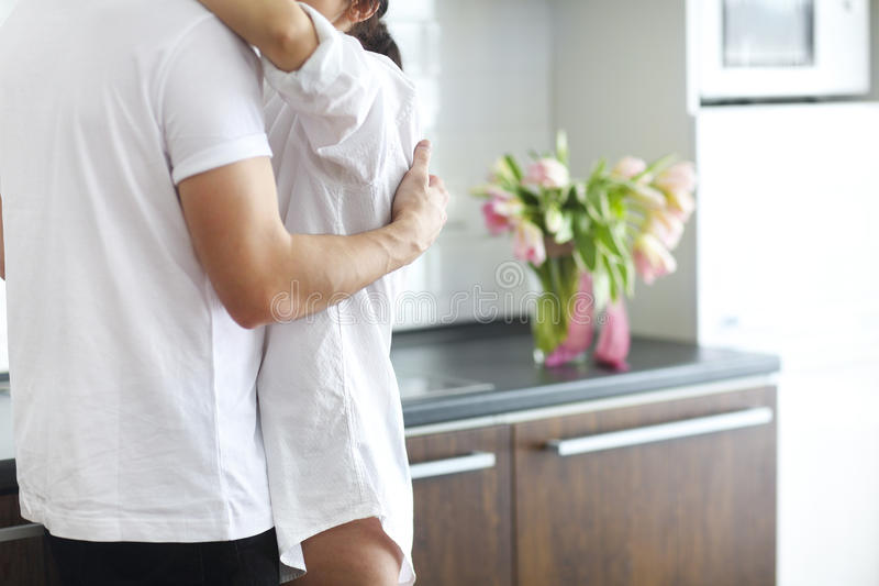Beijos e abraços dos pares na cozinha na manhã fotos de stock royalty free