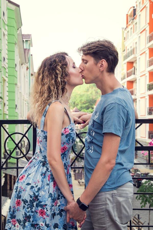 Beijos heterossexuais bonitos dos pares no balcão Casas urbanas coloridos no fundo imagem de stock