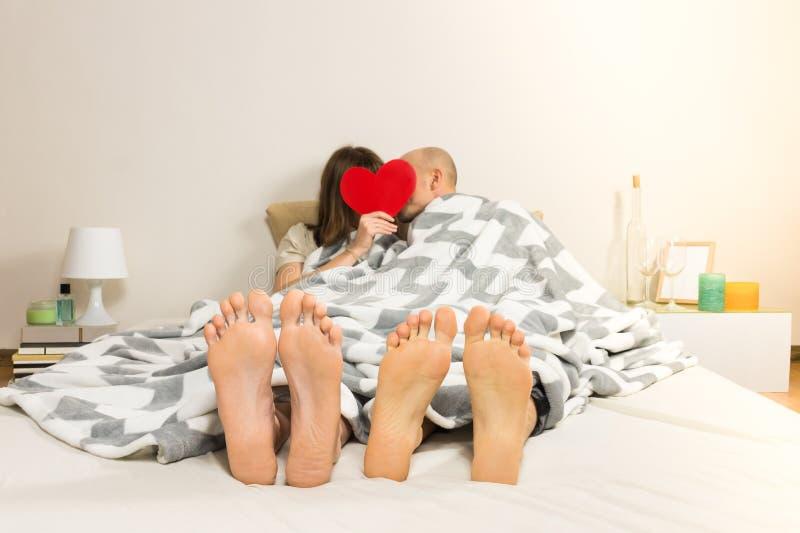 Beijos novos dos pares na cama no quarto moderno minimalistic fotografia de stock
