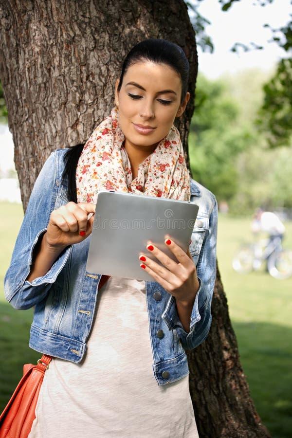 Beiläufige Frau, die draußen Tablette PC verwendet lizenzfreies stockbild