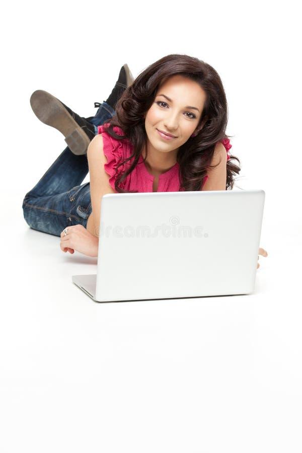 Beiläufige Frau, die mit Laptop sich entspannt stockfotos