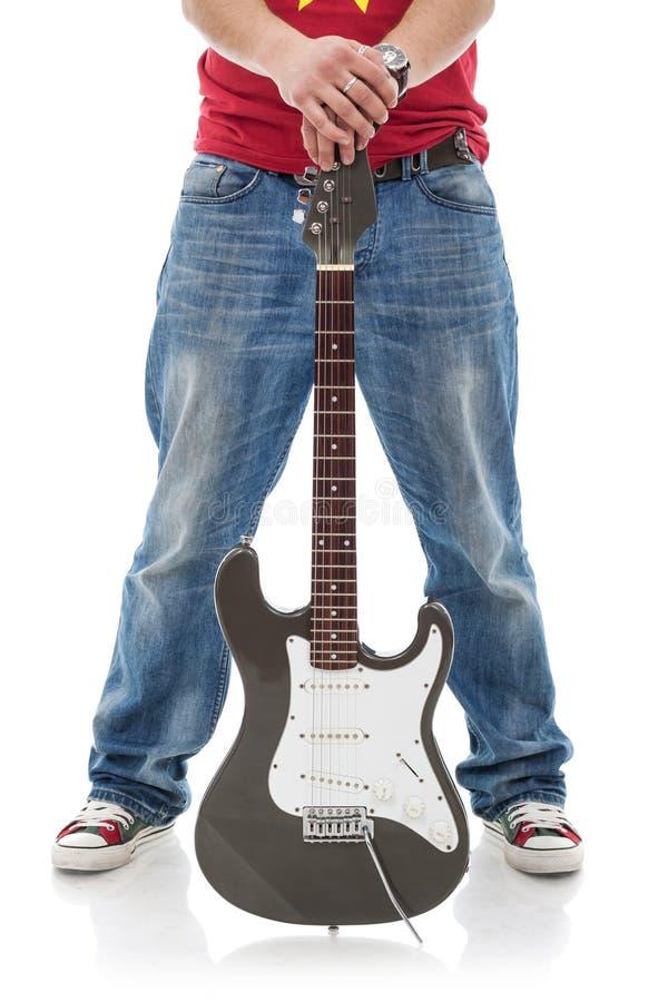 Beiläufige Manngitarre zwischen Fahrwerkbeinen stockfotos