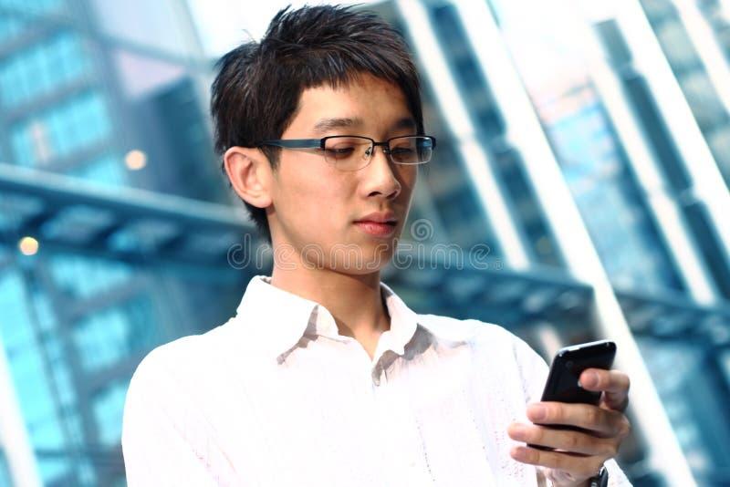 Beiläufiger asiatischer Geschäftsmann, der auf seinem Handy texting ist lizenzfreies stockbild