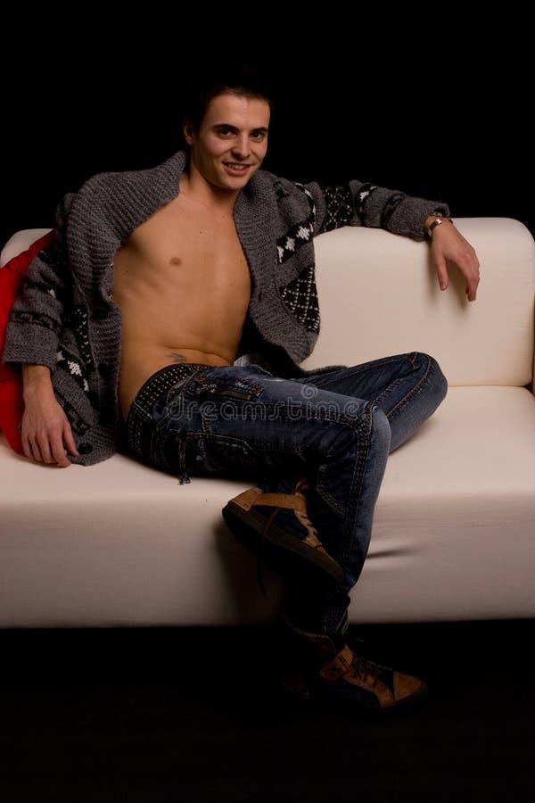 Beiläufiger Junge, der auf Couch sich entspannt stockfoto