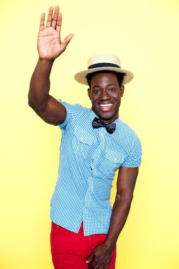 Beiläufiger junger afrikanischer Kerl, der mit dem angehobenen Arm aufwirft stockbilder