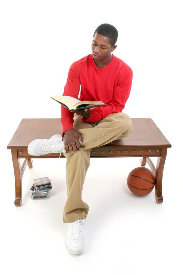 Beiläufiger Mann, der auf Tabellen-Lesebuch sitzt stockfotografie
