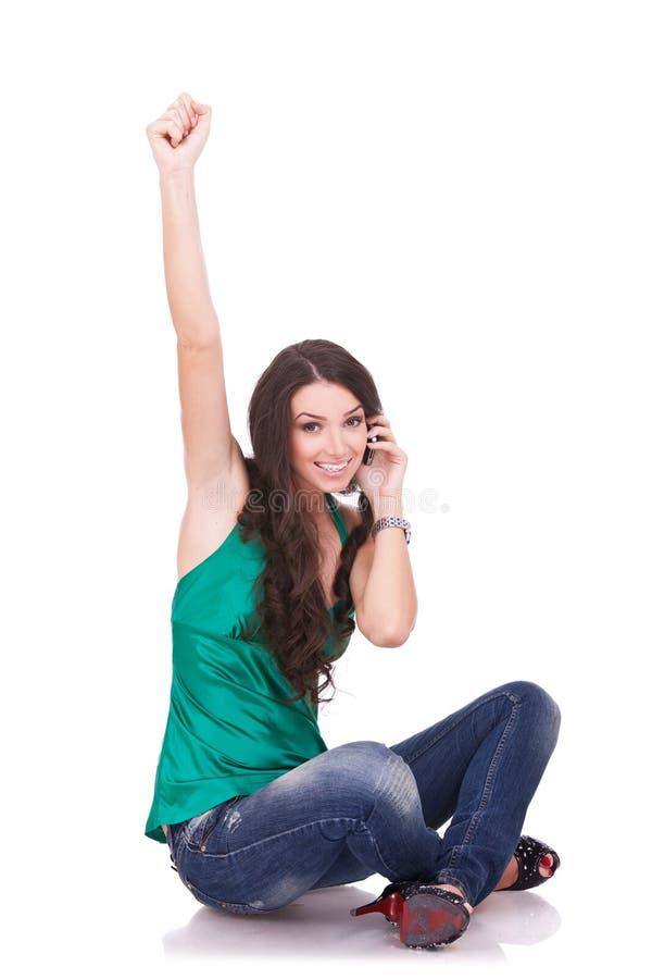 Beiläufiges Mädchen, das während des Telefonaufrufs zujubelt stockfotos