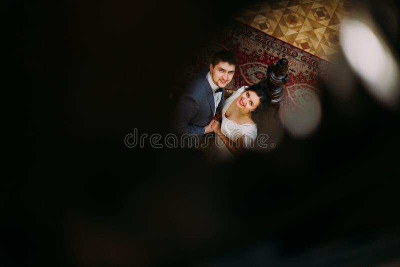 Beiliegende Draufsicht über schöne junge Braut und hübschen den Bräutigam, die an der alten Treppe mit dem Hintergrund von herrli lizenzfreies stockfoto