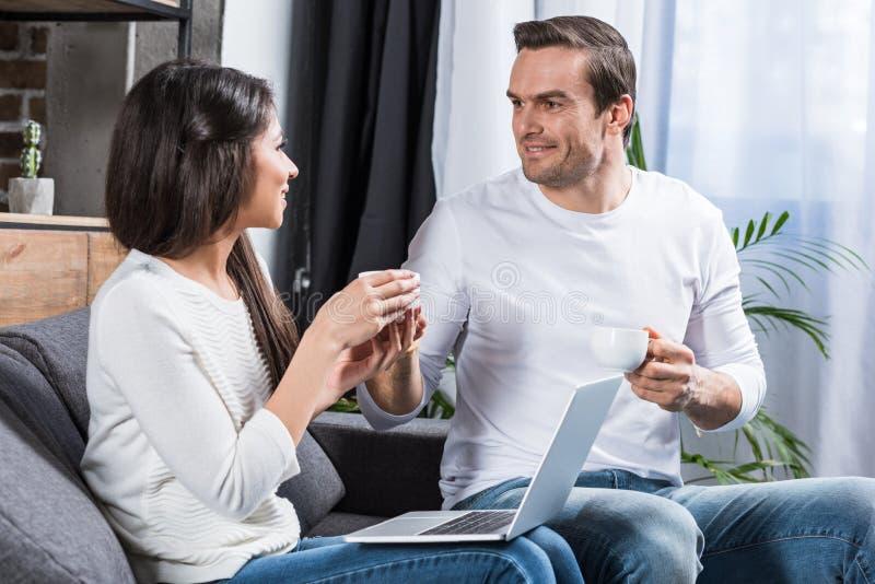 beim Trinken des Tees lächelnde und sprechende Paare und Anwendung des Laptops stockbilder