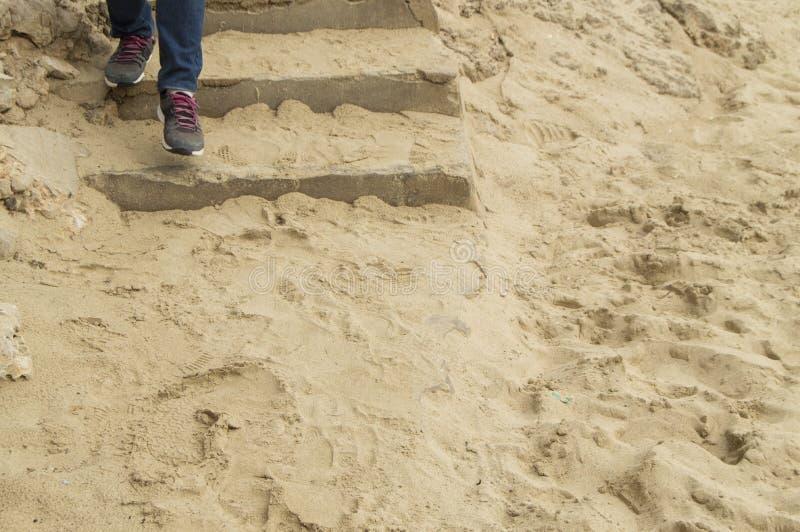 Beine in den Jeans und in Turnschuhen, die ein Steintreppenhaus bedeckt mit Sand, dem Konzept von Tourismus, Reise und Erforschun stockbild
