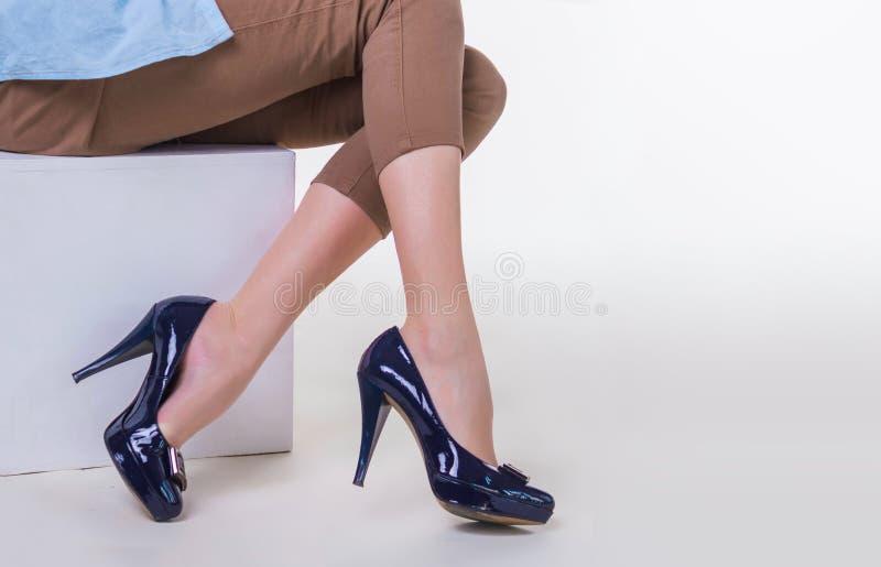 Beine der dünnen jungen Frau in den stilvollen Stöckelschuhen, die auf weißem Hintergrund sitzen lizenzfreies stockfoto