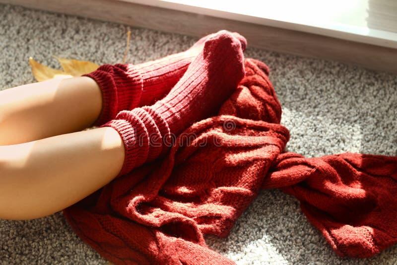 Beine der Frau in den warmen Socken, die zu Hause am Herbsttag stillstehen stockbilder