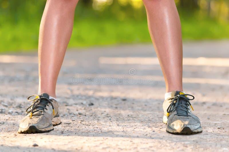 Beine der jungen Sportfrau, die auf der Straße staing ist stockfotografie