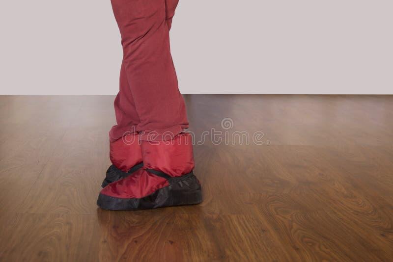 Beine des Balletttänzers in der fünften Position mit roten Fußwärmern lizenzfreie stockbilder