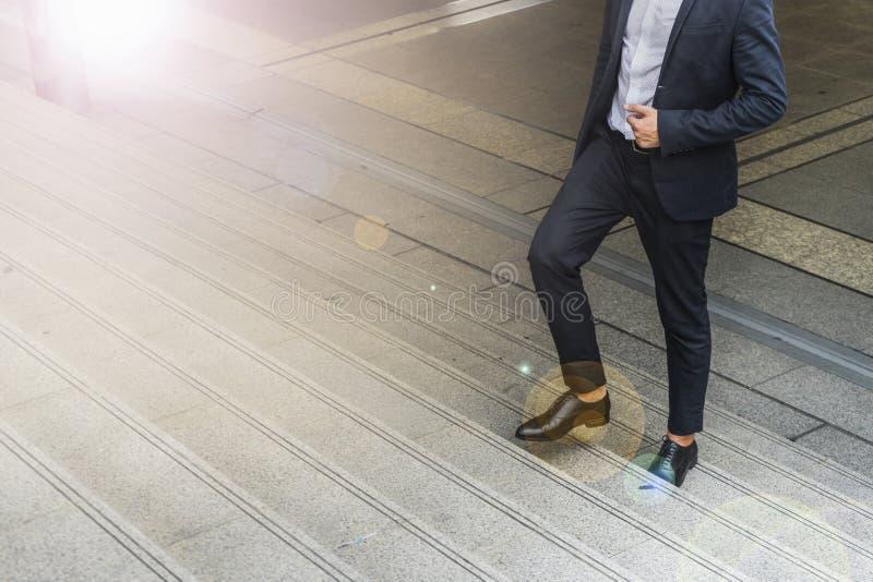 Beine des Geschäftsmannes tragen schwarzen Anzug gehend, Treppe in der modernen Stadt steigernd, wachsen Geschäft und Erfolgskonz stockfoto