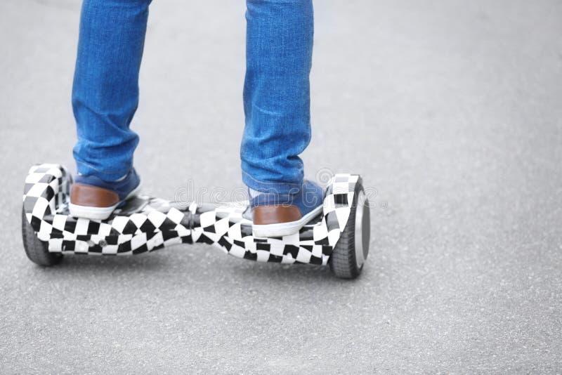 Beine des Jugendlichreitens auf gyroscooter stockbild