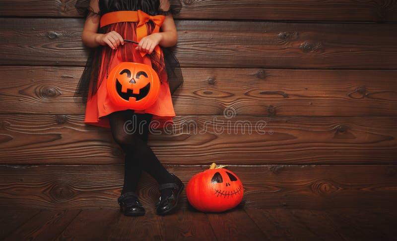 Beine des Kindermädchens im Hexenkostüm für Halloween mit Kürbis stockfoto