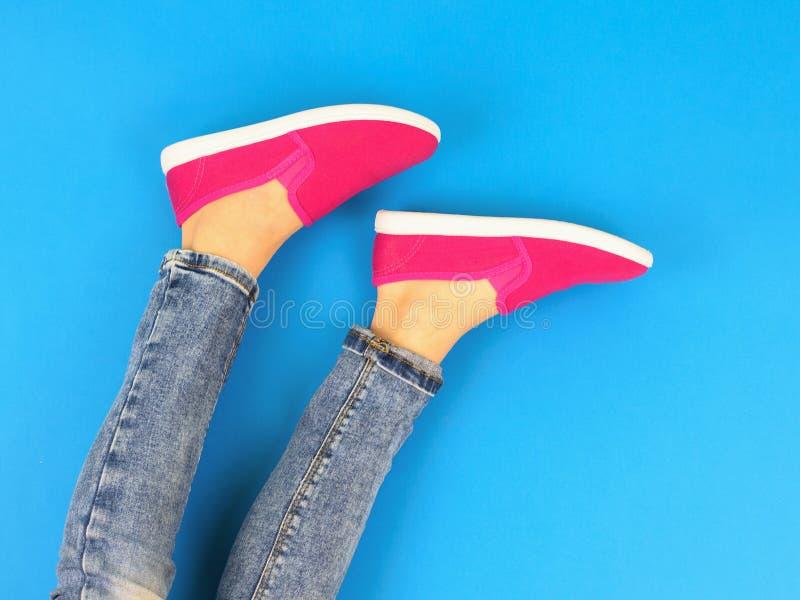 Beine des Mädchens in den roten Turnschuhen auf dem blauen Boden Die Ansicht von der Oberseite stockfotografie