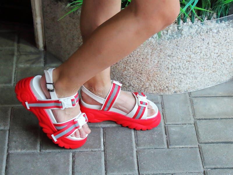 Beine des Mädchens in den Sandalen auf einem Hoch stockfoto