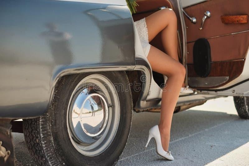 Beine des Mädchenverlassens ein altes Auto junge Frau in den Schuhen der hohen Absätze Fahreröffnungstür des Weinleseautomobils f stockfoto