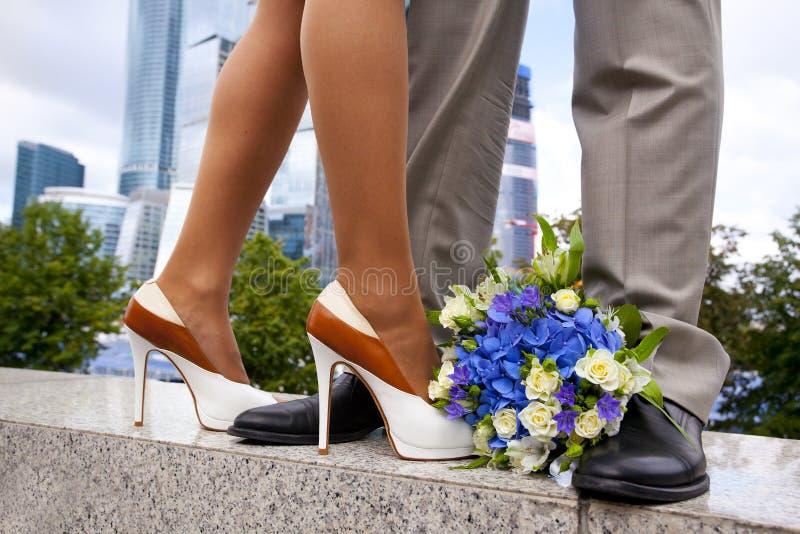Beine des Mannes und der Frau - Braut und Bräutigam - und Hochzeitsblumenstrauß von weißen und blauen Blumen stockfotografie