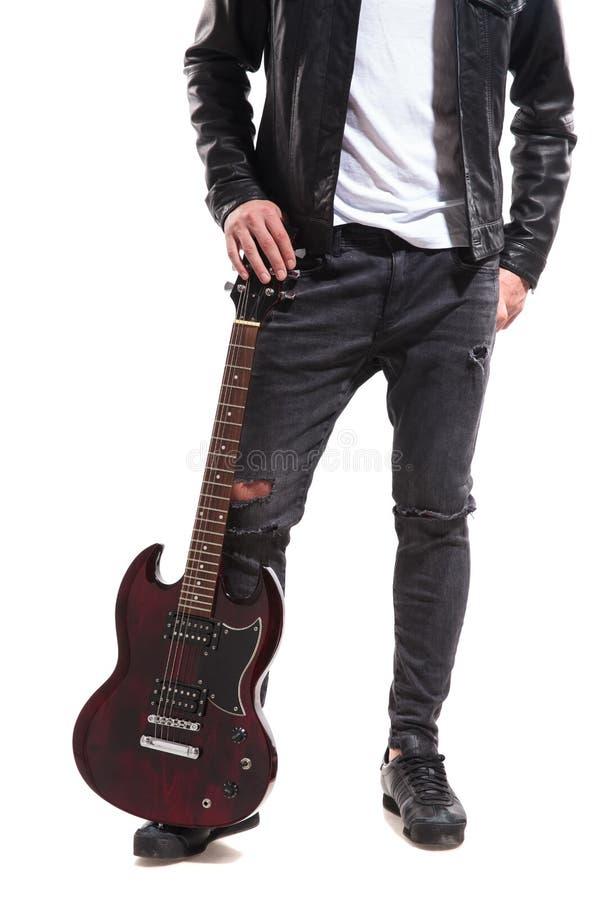Beine des Rockers seine Gitarre auf dem Boden halten lizenzfreie stockfotografie