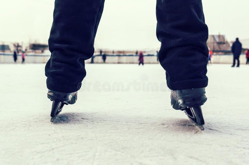 Beine des Schlittschuhläufers in der Bewegung an Eisbahn stockfotografie