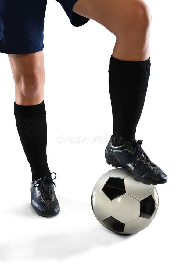 Beine des weiblichen Fußball-Spielers, der auf Ball tritt stockbild
