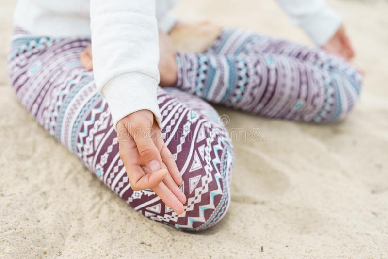 Beine, die auf dem Sand, das Mädchen im Lotussitz, Finger sitzen lizenzfreies stockbild
