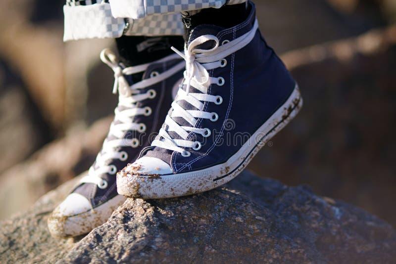 Beine, die blaue schmutzige Turnschuhe mit weißen Spitzeen tragen stockbild