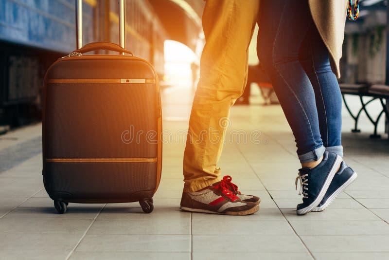 Beine, die das glückliche Umarmen der Paare in der Bahnstation eines Landes nach Ankunft im Herbst mit einem warmen Sonnenlicht l lizenzfreies stockfoto