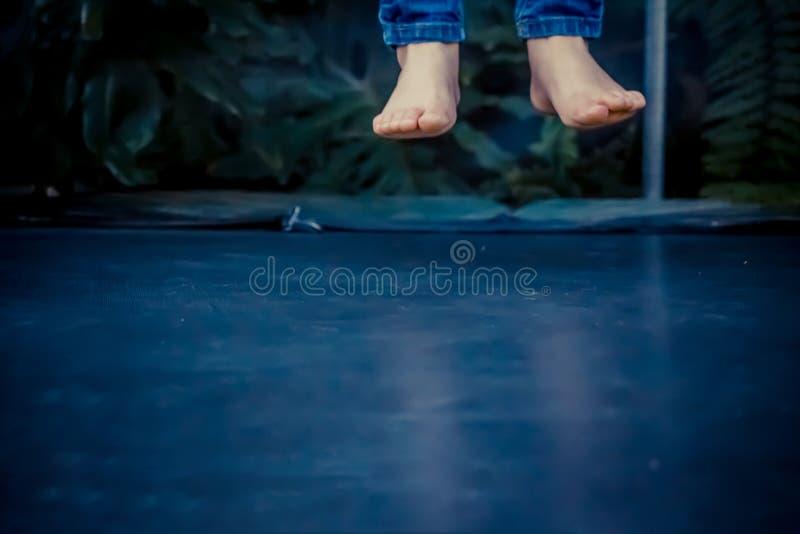 Beine, die in die Luft nachdem dem Springen auf die Trampoline schwimmen stockfotografie