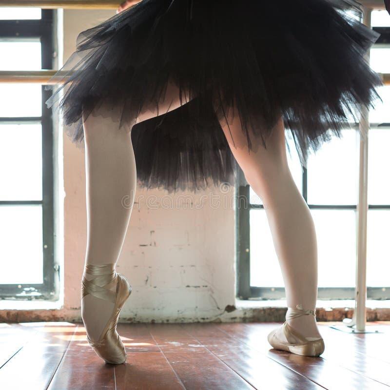 Beine einer Ballerinanahaufnahme Die Beine einer Ballerina im alten pointe Wiederholungsballerina in der Halle Konturnlicht vom F lizenzfreie stockfotos